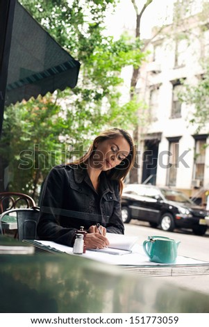 Young woman writing at sidewalk cafe - stock photo