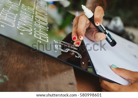 Young woman writing cafe menu on the glass using marker, lettering, hipster style