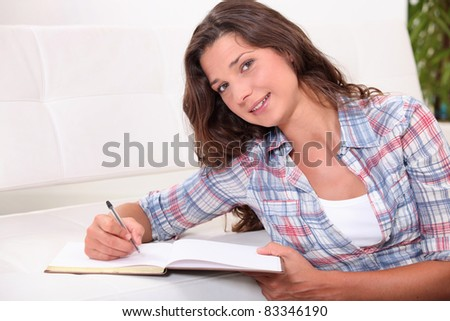 young woman writing on a notebook on a white bench - stock photo