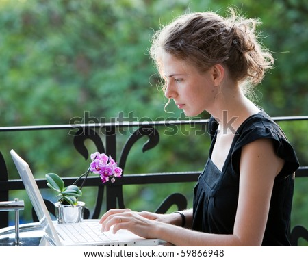 young woman writing on a white laptop computer on the balcony - stock photo