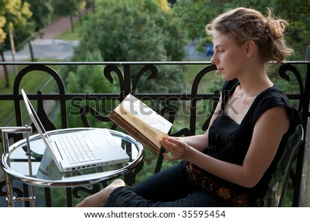 young woman writing on a white modern laptop computer and reading a book on a balcony in art nouveau - stock photo