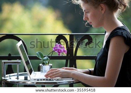 young woman writing on a white modern laptop computer on a balcony in art nouveau