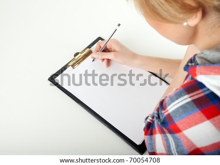 young woman writing on black clipboard - stock photo