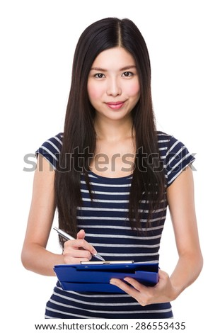 Young woman writing on clipboard