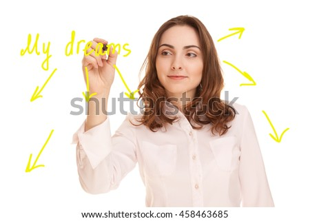 Young woman writing scheme called My dreams on red background - stock photo