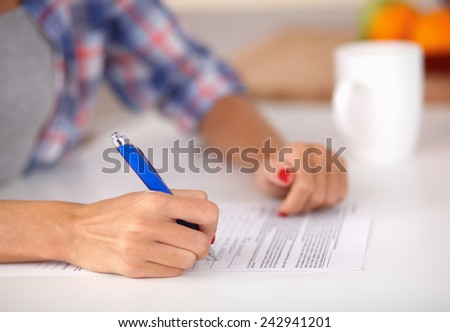 Young woman writing something in her note pad - stock photo