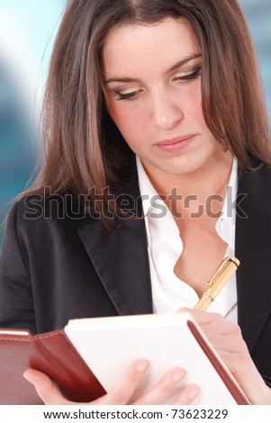 Young woman writing something using a golden pen - stock photo