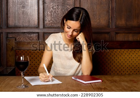 young woman writing with a glass of wine. - stock photo