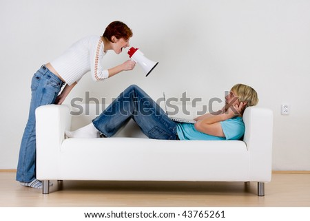 Young woman yelling through a megaphone at a man laying on a couch with his fingers in his ears. - stock photo