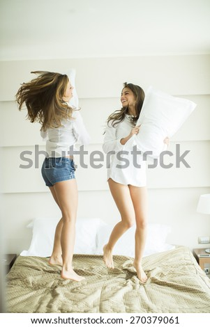 Young women ahving a pillow fighting on the bed - stock photo