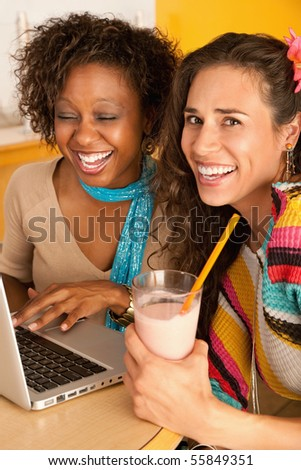 Young women at a cafe using a laptop computer. Vertical shot. - stock photo