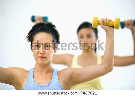 Young women at gym lifting hand weights. - stock photo