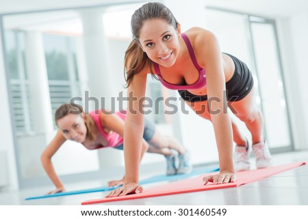Young women at the gym doing push ups on a mat, fitness and healthy lifestyle concept - stock photo