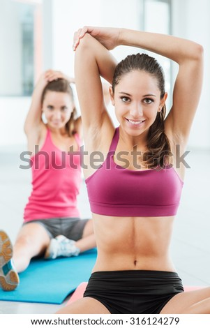 Young women at the gym sitting on a mat and doing stretching exercises for arms - stock photo