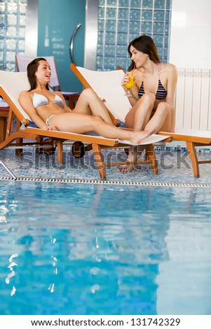 Young women by the pool - stock photo