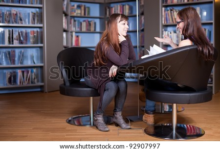 Young women chatting in library - stock photo