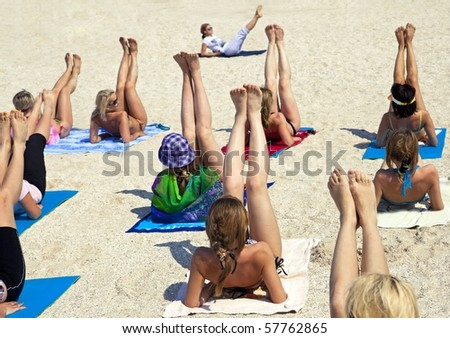 Young women doing fitness exercise on a beach - stock photo