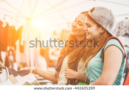 Young women doing shopping at the weekly cloth market at sunset with back lighting - Cheerful girls enjoying sale time in summer - Friendship and shopping addiction concept - Vintage retro filter - stock photo
