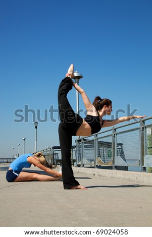 young women doing yoga on a pier - stock photo