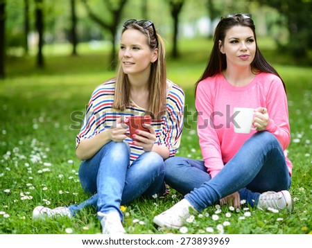 Young women drinking coffee at park and enjoying summer day - stock photo