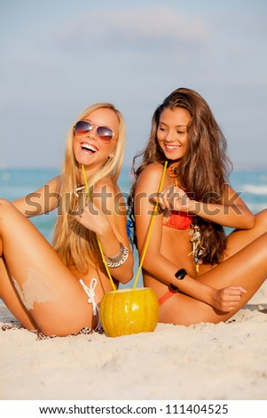 young women drinking on beach summer vacation or holiday - stock photo