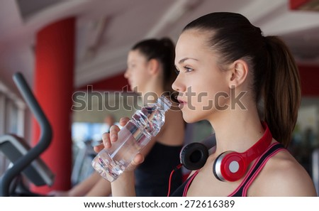 young women drinking water after sports. Fitness gym.