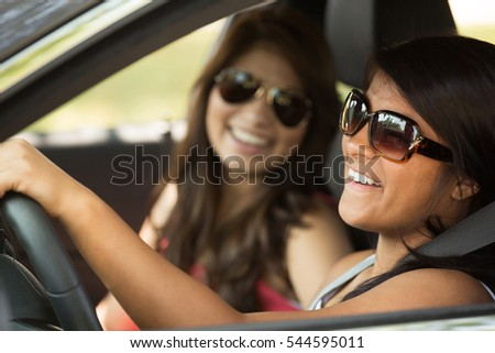 Young women driving. Teenage friends driving a car.