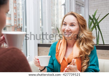 Young women emotionally talking and drinking coffee in a small cafe