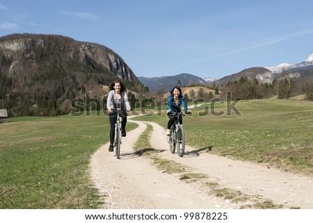 Young women enjoying sunny day on mountain bike - stock photo