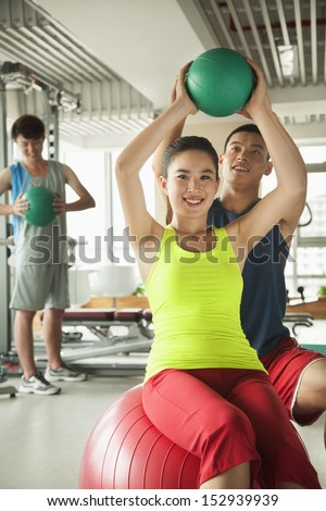 Young women exercising with her personal trainer in the gym - stock photo