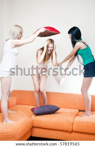 Young women fighting on pillows. Bright white colors. - stock photo