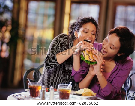 Young women fighting to take bite of hamburger - stock photo