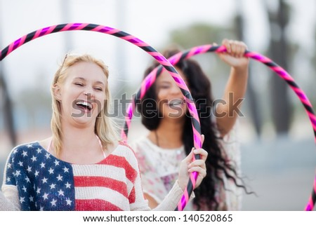 Young women Friends on the boardwalk at the Beach playing with Hula Hoops - stock photo