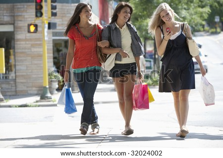 Young women friends shopping and texting on a cell phone - stock photo