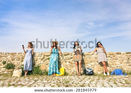 Young women girlfriends using smartphone outdoors with mutual disinterest towards each other - Female modern friendship with technology addiction in actual lifestyle - Sunny afternoon color tones - stock photo