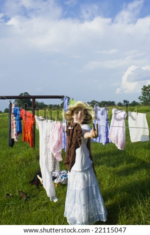 Young women hanging clothes out on the line to dry in the summer - stock photo