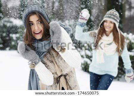 Young women have fun during the snowball fight - stock photo