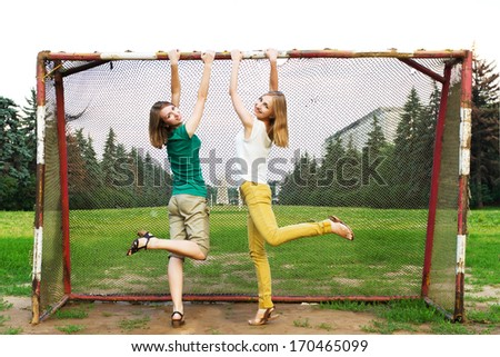 Young women having fun hanging by vintage soccer goal. Attractive girls having fun on a soccer field