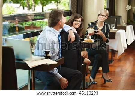 Young women having sweets in cafe, talking with businessman sitting at next table, smiling. - stock photo