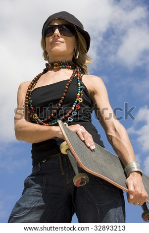 Young women holding a skate with blue sky on background - stock photo