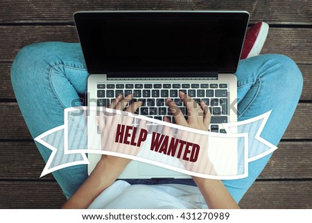 Young women holding laptop writen Help Wanted on it - stock photo