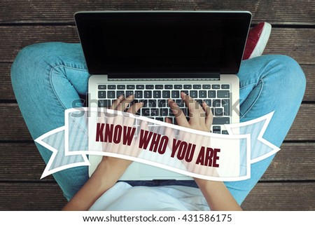 Young women holding laptop writen Know Who You Are  on it