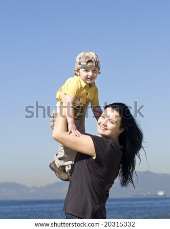 young women holding little boy on the beach - stock photo