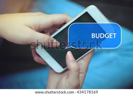 Young women holding mobile phone writen Budget on it - stock photo
