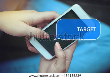 Young women holding mobile phone writen Target on it - stock photo