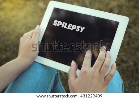 Young women holding tablet writen Epilepsy on it - stock photo