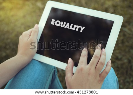 Young women holding tablet writen Equality on it - stock photo
