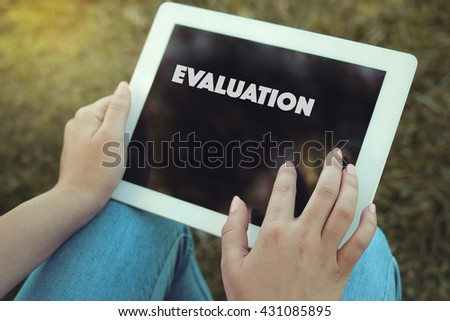 Young women holding tablet writen Evaluation on it - stock photo