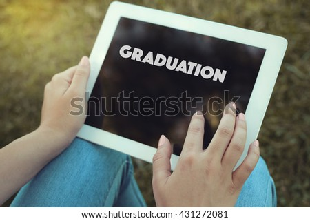 Young women holding tablet writen Graduation on it - stock photo