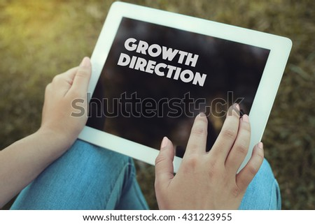 Young women holding tablet writen Growth Direction on it - stock photo